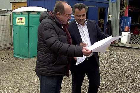 Männer mit Plan auf einer Baustelle