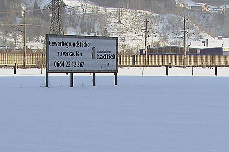 Schild eines Immobilienmaklers auf verschneiter Wiese neben der Eisenbahn