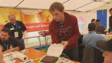 Ein teilnehmer der GrillWM präsentiert sein Fleisch der internationalen Jury