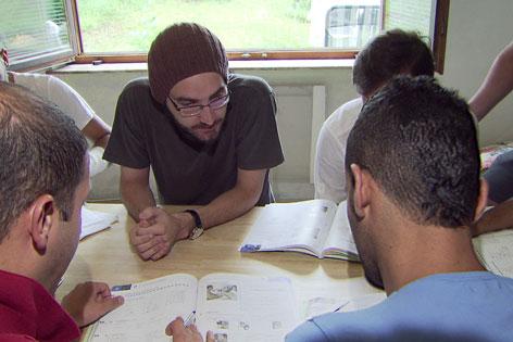 Freiwillige Flüchtlingshelfer beim Unterrichten