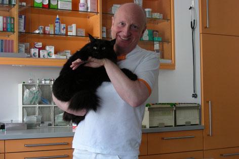 Tierarzt Bernhard Anker mit einer großen schwarzen Katze im Arm