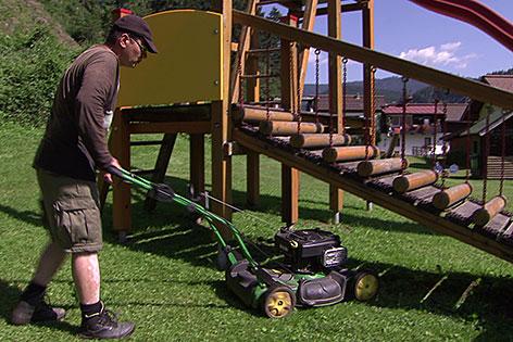 Flüchtling beim Rasenmähen auf Kinderspielplatz