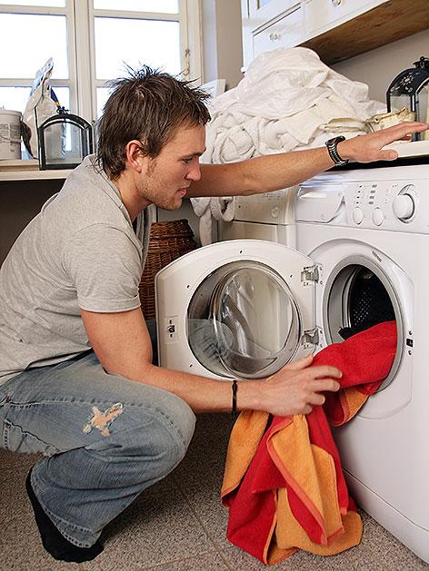 Mann beim Ausräumen einer Waschmaschine