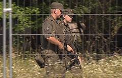 Bewaffnete Soldaten gehen am Zaun des Flüchtlingslagers Streife