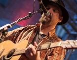 Mann mit Gitarre und Mikrofon beim Americana Fest Konzert von Sparkledrive