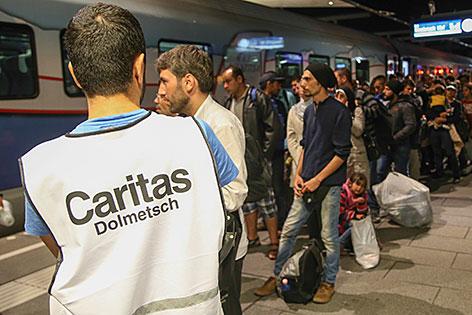 Dolmetscher der Caritas mit Flüchtlingen am Salzburger Hauptbahnhof
