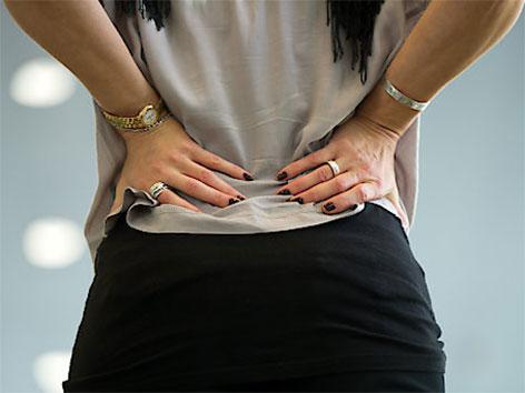 Frau fasst sich mit beiden Händen an den Rücken
