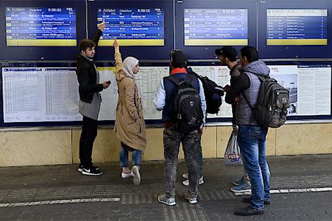 Flüchtlinge vor einer Zuganzeigetafel