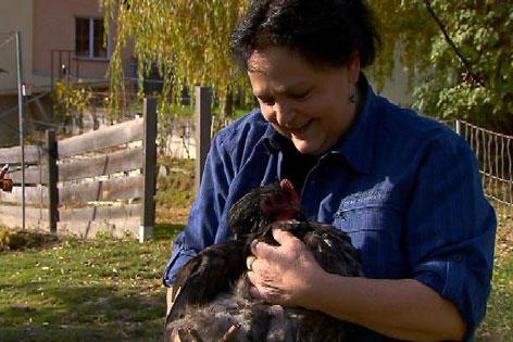 Hühnerhalterin Alexandra Zangerl mit einem schwarzen Hahn im Arm