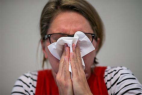 Frau mit Schnupfen putzt sich die Nase