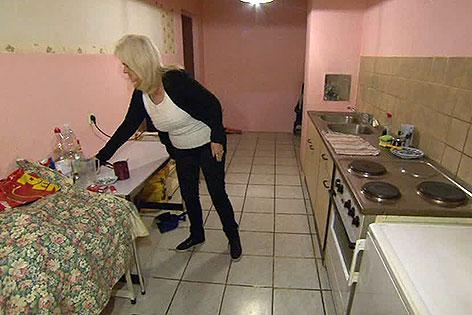 Frau in Küche einer Gemeindewohnung