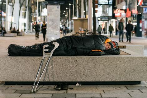 Obdachloser schläft auf Bank