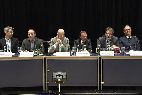 Teilnehmer am Podium einer Bürgerversammlung zur Unterbringung von Flüchtlingen in Liesing