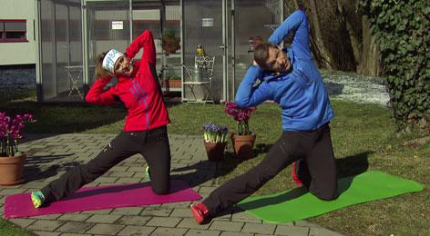 Doresia Krings und Michael Mayrhofer dehnen den Oberkörper