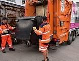 Müllmänner entleeren Mülltonne in Mülllastwagen