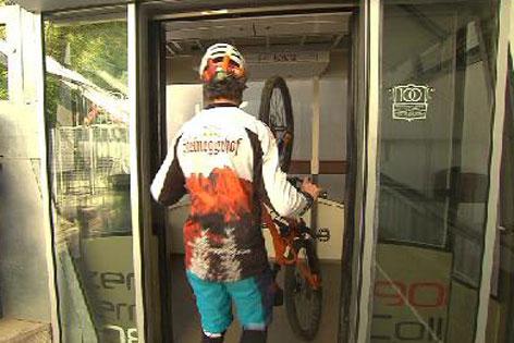 Downhiller trägt Mountainbike in eine Gondel