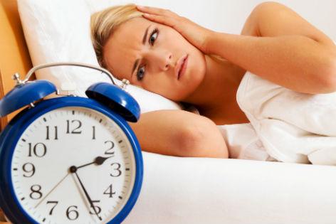 Frau liegt im Bett im Vordergrund ein blauer Wecker