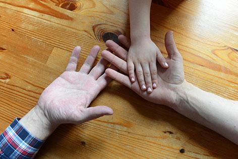 Hände eines homosexuellen Paares und eines Kindes.