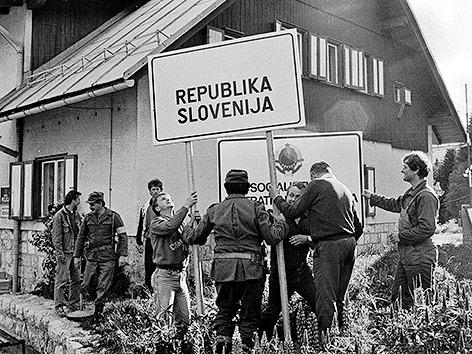 """Männer der slowenischen Miliz mit einer Tafel mit der Aufschrift """"Republik Slowenien"""" am 29. Juni 1991."""