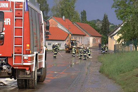 Feuerwehr beseitigt Schlamm mit Traktor von der Straße