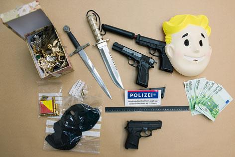 von Polizei beschlagnahmte Waffen, Bargeld, Masken