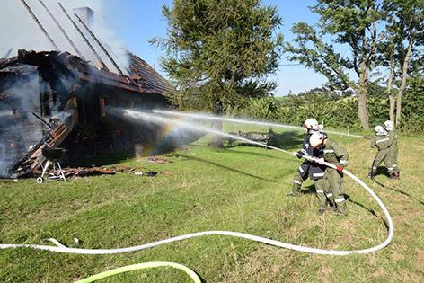 Feuerwehrmänner bei Löscharbeiten bei einem Wohnhausbrand in Zöbern