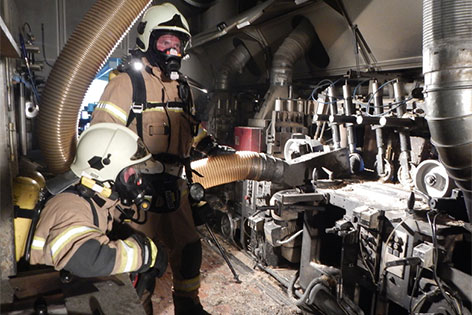Feuerwehrleute mit schwerem Atemschutz bei Maschine