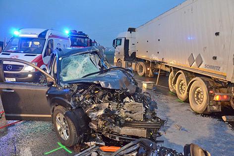 Unfallwrack des Pkw steht neben Lkw