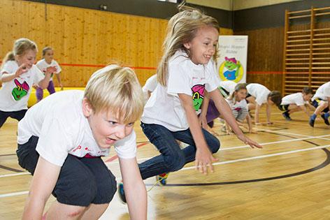 Kinder bei Turnstunde in Turnhalle einer Schule