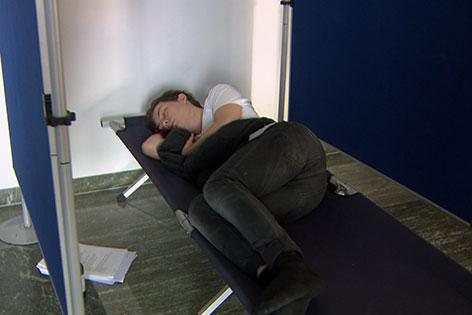 Schlafender Teilnehmer auf Feldbett bei Poetry Slam in der Stadt Salzburg