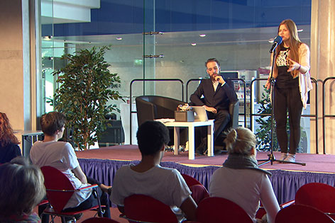 Teilnehmerin und Zuschauer bei Poetry Slam in der Stadt Salzburg