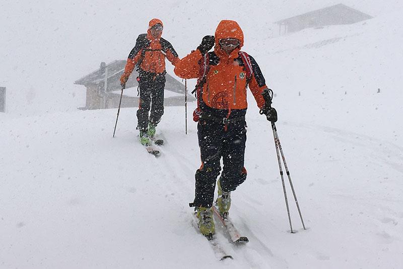 Bergretter bei Sucheinsatz im Schneetreiben im Winter vor Almhütten (Genneralm, Osternhorngruppe)