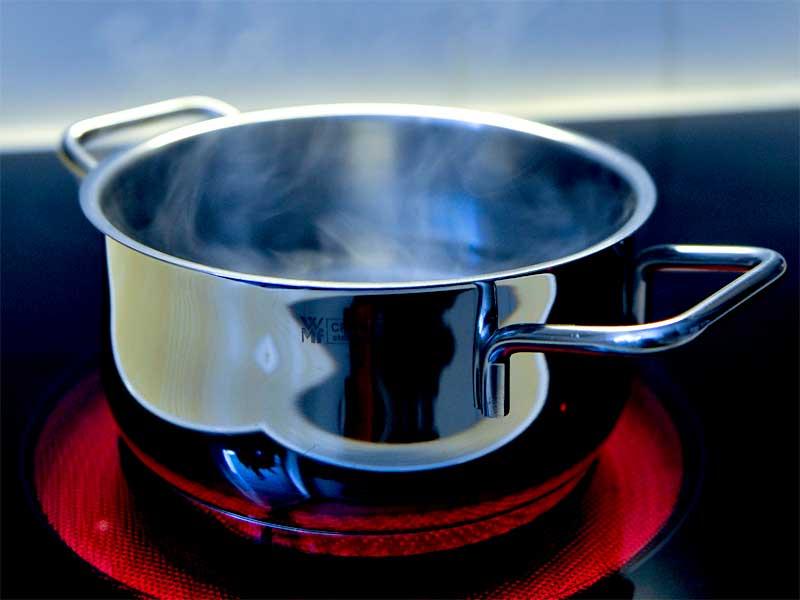 Kochtopf mit kochendem Wasser auf glühender Herdplatte