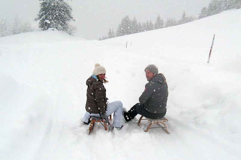 Rodler auf Schlitten im Neuschnee
