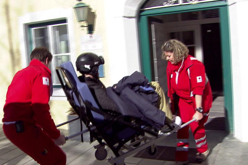 Verletzter Skifahrer wird vom Roten Kreuz in Arztpraxis eingeliefert