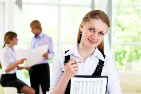 Junge Frau mit Klemmmappe steht im Vordergrund, im Hintergrund zwei Kollegen, die einen Plan anschauen