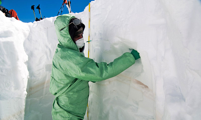 Forscher in Schneeloch untersucht Schnee
