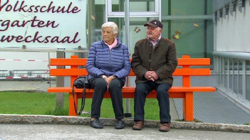 Menschen sitzen auf orangefarbener Bank
