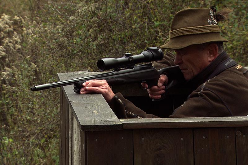 Jäger mit Gewehr auf Hochstand