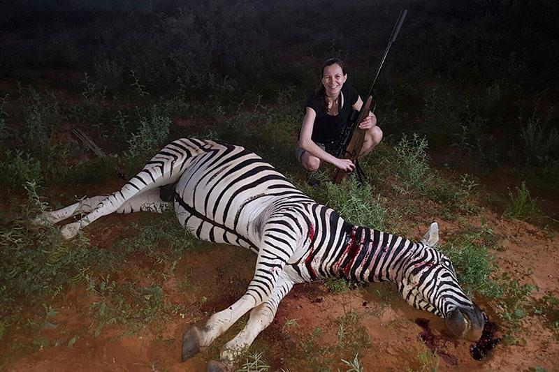 Jägerin posiert mit erlegtem Zebra und Gewehr in Südafrika