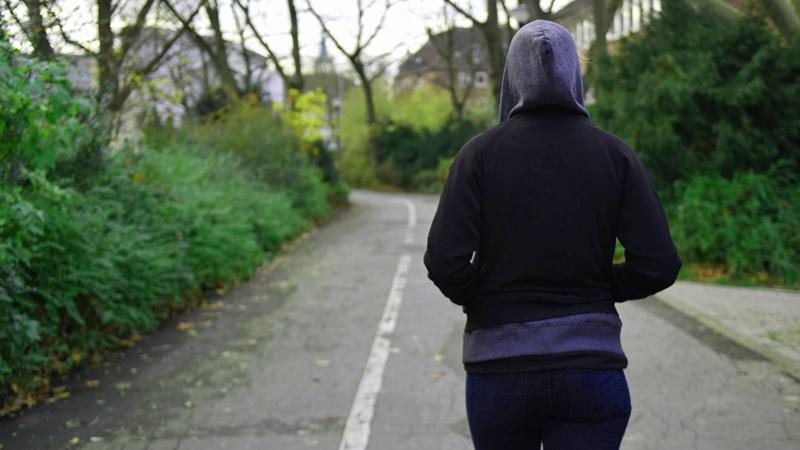 Mädchen geht allein den Weg entlang