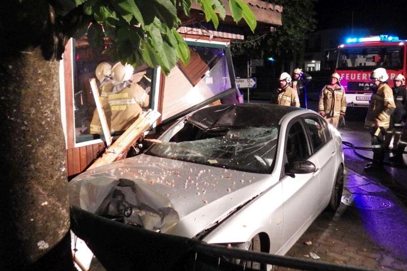 Auto nach Unfall an Baum mit Feuerwehrleuten