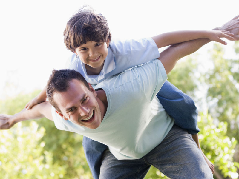 Vater mit Sohn am Rücken
