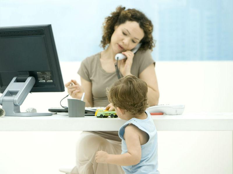 Frau telefoniert Kleinkind spielt im Vordergrund
