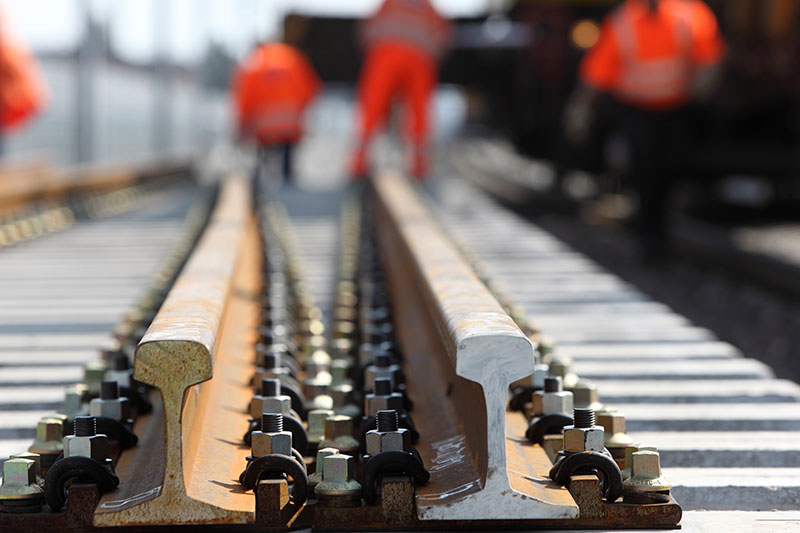 Neue Gleise mit Bauarbeitern bei Gleiserneuerungsarbeiten auf einer Baustelle