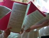 Kinderchor mit Notenmappen beim Singen
