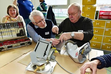 Freiwillige beim Repair Cafe reparieren Schneidemaschine