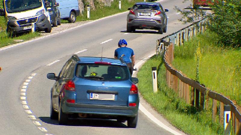 Auto überholt Rennradfahrer