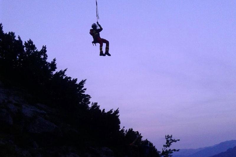 Flugretter hängt am Rettungstau eines Notarzthubschraubers in Bergen in der Abenddämmerung