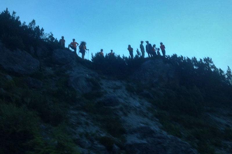 Bergretter über steilem Abhang in der Abenddämmerung